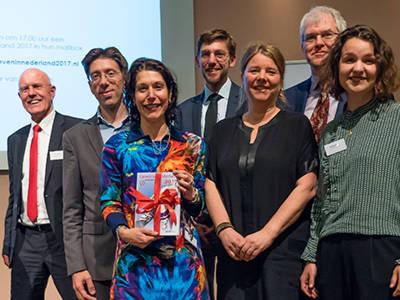 mr. Maril Gelauff (ministerie van V&J) met het eerste exemplaar van 'Geven in Nederland 2017' temidden van de VU-wetenschappers